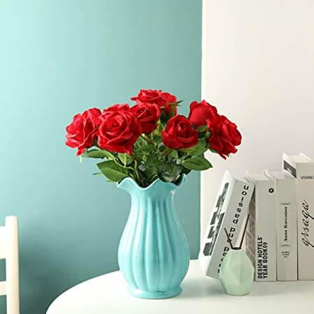 En esta imagen se muestran unas nueve rosas en un jarrón azul sobre una mesa con libros y de fondo una esquina de una pareded en la esquina de la izquierda es azul y la de la derecha es blanco.