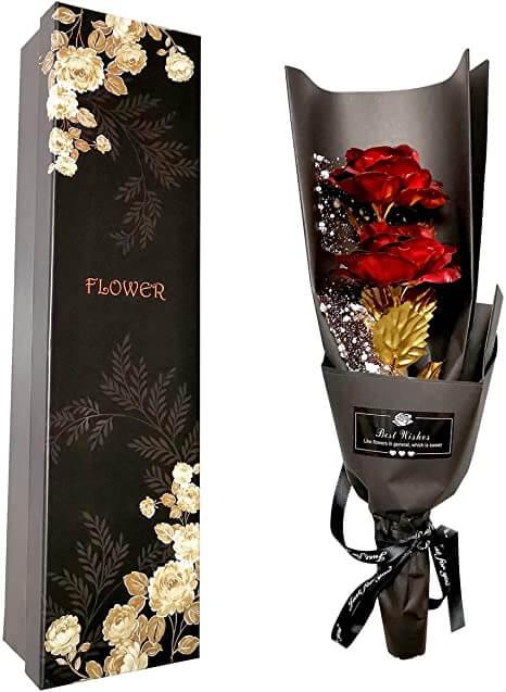 Foto de una rosa roja eterna envuelta en plastico brillante, duro y negro. La rosa eterna viene en una caja negra decorada con dibujos de rosas. Muy elegante y bonita