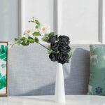 En esta foto sale seis rosas negras de un florero blanco y estrecho . Esta puesto encima de la mesa de un salón se ve el sofá de fondo.
