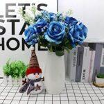 Una foto de rosas azules dentro eu jarrón blanco y con libros de fondo