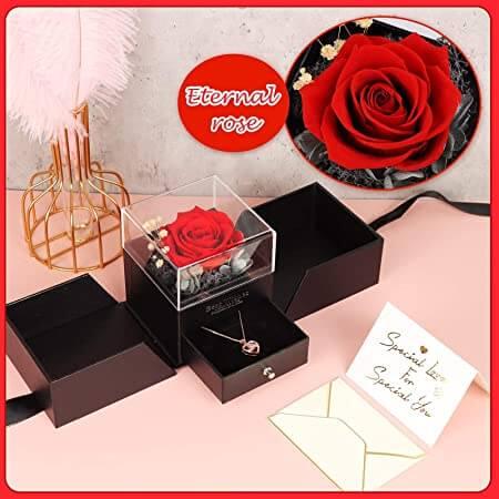 En esta foto sale la caja de rosa abierta mostrando un cajón secreto debajo de la rosa. En ese cajón se muestra una joya. Esta caja esta sobre unsa mesa rosa y con una carta que dice especial para ti.