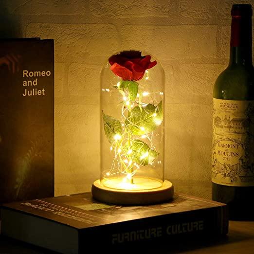 En la foto aparece una rosa eterna en un recipiente transparente con luces para iluminar la rosa eterna. De fondo aparece un libro de Romeo y Julieta y una botella de vino