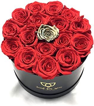 comprar-flores-a-domicilio-madrid-baratas-envio-Es una imagen de una caja negra y redonda en la cual esta abierta y se muestran completa de rosas rojas y una rosa dorada justo en el medio.
