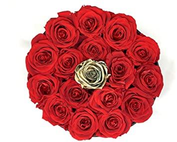 flores-a-domicilio-madrid-baratas-Es una imagen de una caja negra y redonda en la cual esta abierta y se muestran completa de rosas rojas y una rosa dorada justo en el medio. Desde la parte de arriba esta echa esta foto